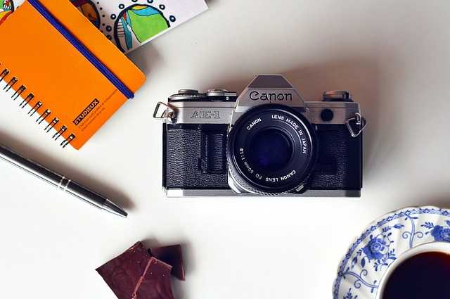 camera, pen, notebook,and cup of tea