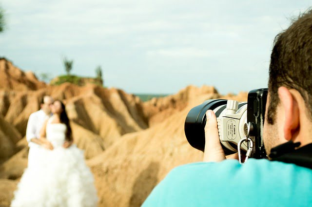 Photographer taking photo of wedding couple