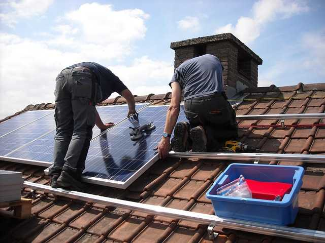 Two workers installing solar on roof